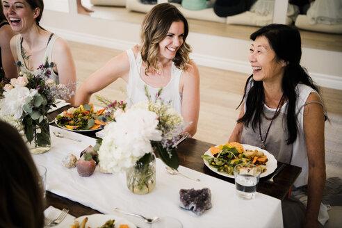 Women enjoying friendship and meal in yoga retreat - CUF45023