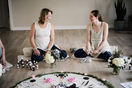 Women around circle in yoga retreat - CUF45032