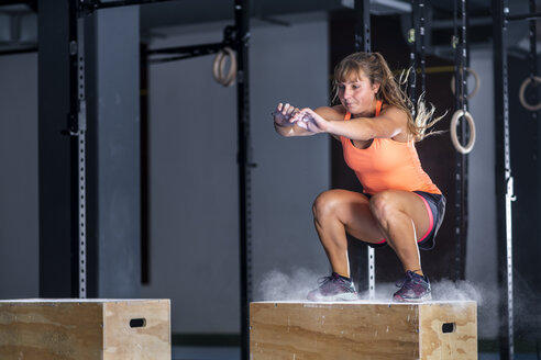 Athletic young woman doing box jump exercise at gym - STSF01757