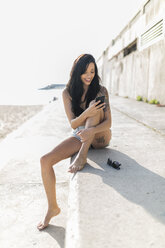 Smiling young woman with nose piercing and tattoo using smartphone near the beach - GIOF04637
