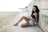 Portrait of tattooed young woman reading a book near the beach - GIOF04643
