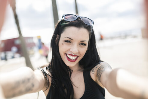 Portrait of happy young woman with nose piercing and tattoos - GIOF04655