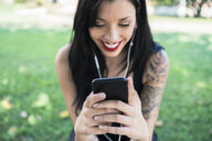 Hands of smiling young woman holding smartphone - GIOF04658