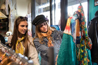 Friends browsing vintage clothes in thrift store - CUF45090
