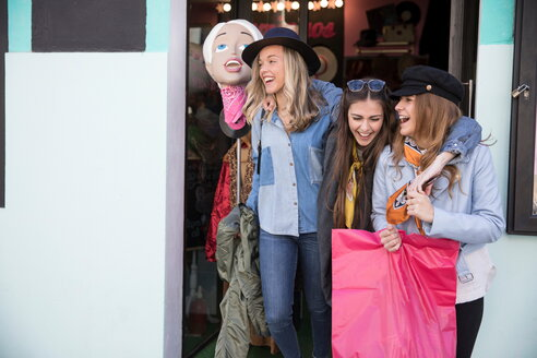 Friends leaving clothing shop smiling - CUF45093