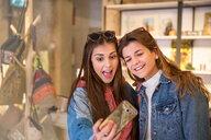 Two friends in shop, taking selfie, using smartphone - CUF45129