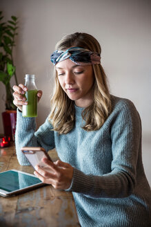 Young woman with vegetable juice looking at smartphone at cafe window seat - CUF45132