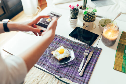 Woman photographing breakfast on mobile phone - CUF45144