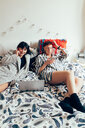 Women relaxing on bed using laptop and mobile phone - CUF45147