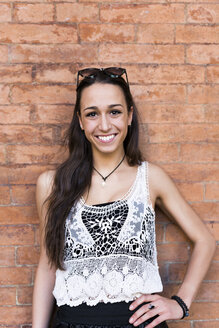 Portrait of fashionable young woman standing in front of brick wall - GIOF04662