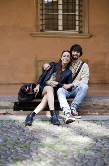 Portrait of happy young couple sitting on steps outdoors - GIOF04665
