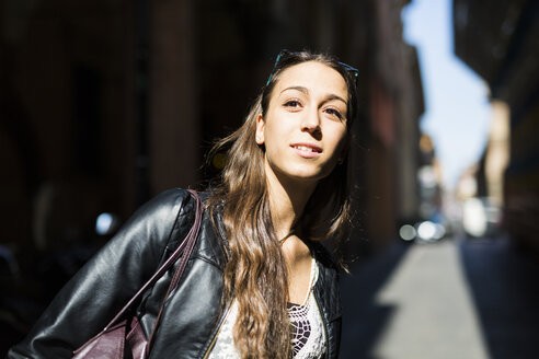 Portrait of smiling young woman in the city looking at distance - GIOF04671