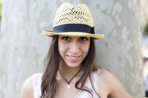 Portrait of smiling young woman wearing straw hat - GIOF04680