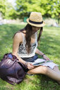 Young student sitting on a meadow in a park using digital tablet - GIOF04683