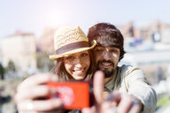 Portrait of happy young couple taking selfie with smartphone - GIOF04695
