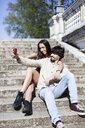 Happy young couple sitting on stairs taking selfie with smartphone - GIOF04698