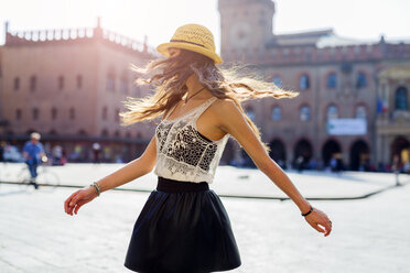 Italy, Bologna, young woman dancing on square - GIOF04701