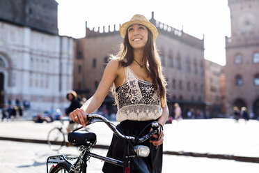 Italy, Bologna, portrait of fashionable young woman pushing bicycle in the city - GIOF04704