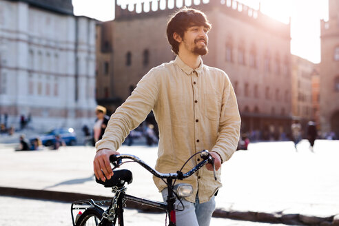 Italy, Bologna, portrait of relaxed young man pushing bicycle in the city - GIOF04707