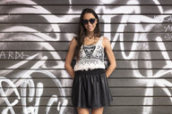 Portrait of fashionable young woman wearing sunglasses standing in front of graffito - GIOF04710