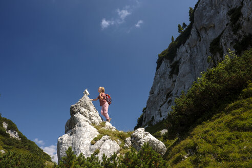 Austria, Ausseer Land, Girl climbing on rocks in the mountains - HAMF00387