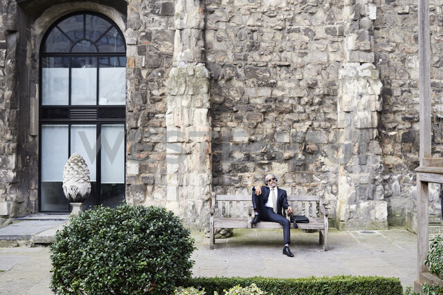 UK, London, senior businessman sitting on bench in a courtyard relaxing while liestening music with headphones - IGGF00612