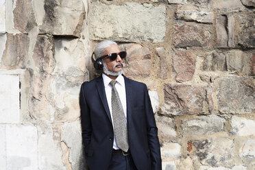 Portrait of senior businessman in blue suit listening music with headphones - IGGF00615