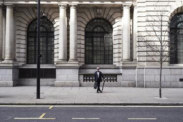 UK, London, stylish senior businessman with briefcase and umbrella standing on pavement - IGGF00618