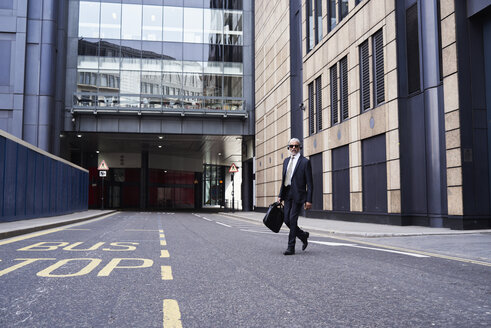 UK, London, senior businessman with headphones crossing the street - IGGF00621