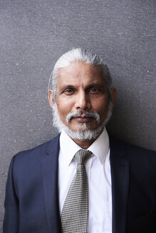 Portrait of senior businessman with grey hair and beard wearing suit and tie - IGGF00624