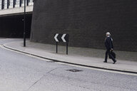Senior businessman with luggage walking on pavement - IGGF00627