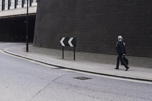 Senior businessman with luggage walking on pavement - IGGF00627