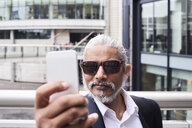 Portrait of grey-haired senior businessman taking selfie with smartphone - IGGF00633