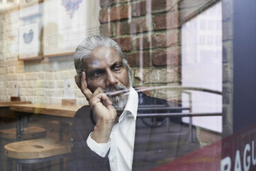 Portrait of pensive senior businessman in a coffee shop looking out of window - IGGF00642