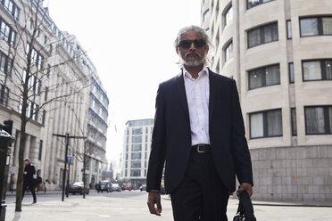 UK, London, UK, portrait of senior businessman walking in the city - IGGF00645