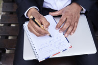 Businessman writing notes in notebook, close-up - IGGF00654