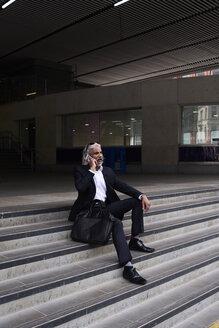 Stylish senior businessman on the phone sitting on stairs outdoors - IGGF00660