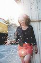 Laughing woman throwing confetti - HMEF00014