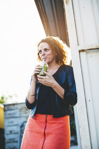 Portrait of woman drinking green smoothie outdoors - HMEF00016