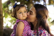 Young woman kissing serious looking baby girl - VABF01620