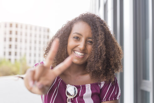 Portrait of smiling young woman showing victory sign - JUNF01472