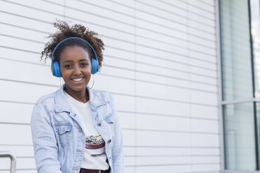 Portrait of smiling young woman listening music with headphones - JUNF01481