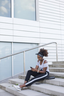 Smiling young woman sitting on stairs looking at smartphone - JUNF01490