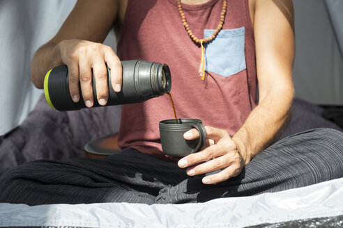 Man sitting in tent pouring coffee into a cup, partial view - JPTF00007