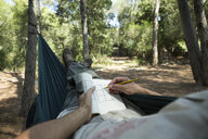 Man lying in hammock in the woods relaxing with puzzle book, partial view - JPTF00010