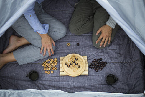 Couple sitting in tent playing board game, partial view - JPTF00013