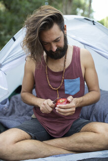 Man sitting in front of a tent peeling an apple - JPTF00019