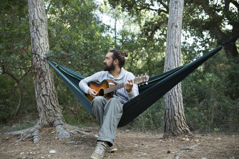 Man sitting in hammock playing guitar in the woods, partial view - JPTF00022