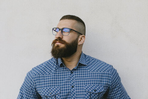 Portrait of bearded hipster businessman wearing glasses and plaid shirt - FMGF00013