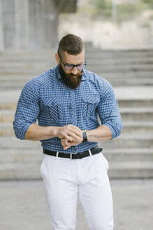 Bearded hipster businessman checking the time - FMGF00016